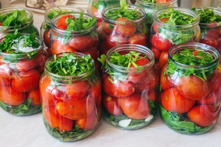 Fermenting vegetables with lots of greens in glass jars. Processing the harvest of tomatoes from home garden