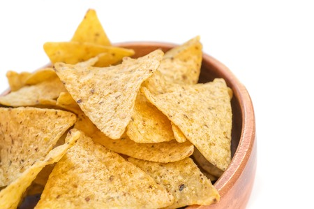 Corn tortillas or nachos, fried over an open fire, lie in a wooden bowl. Copy space. Archivio Fotografico