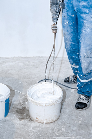 Electric mixer mixes paint in a white bucket. Paddle mixer over a bucket of white paint for the wall, tools and accessories for DIY, close-up workflow.