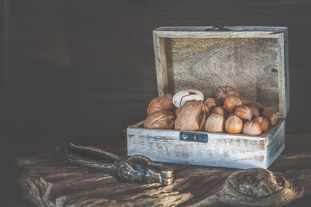 Pecan nuts and macadamia walnuts in a box with pegs for nuts on a wooden Stok Fotoğraf