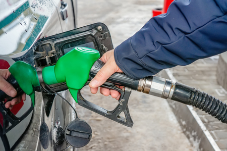 Man fills the gas tank of the car. The concept of price changes for petroleum products and petrol. Stock Photo