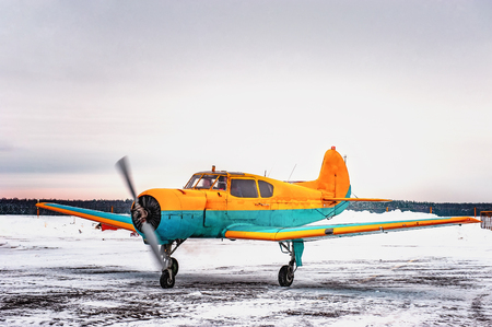 A small yellow plane with a blue stripe landed in the winter at an airport parking lot. 写真素材