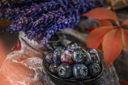 Blue berries blueberries in wicker white basket with autumn leaves