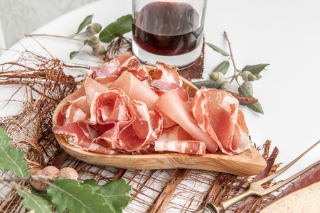 Parma flavored ham in spices, thinly sliced on a white table with red wine bread and antique cutlery.