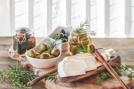 Aged brie cheese on a White dish with olives and Provence herbs wooden table.