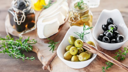 Aged brie cheese on a White dish with olives and Provence herbs wooden table. Stockfoto