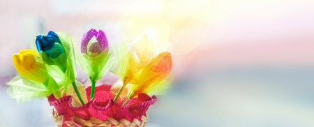 Delicate multicolored buds of tulips handmade from thin paper on a blurred on a sunny day.