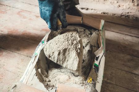 Cement w proszku w worku z cementem, ręka trzyma kielnię miarka cementu w proszku do prac budowlanych.