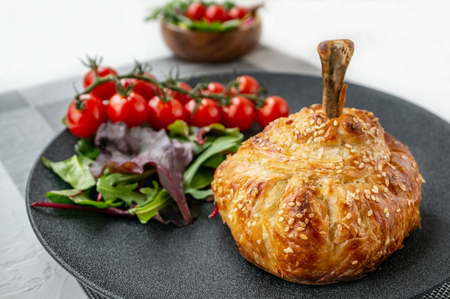 Chicken drumstick in dough baked in the oven with potatoes, tomatoes, onions and spices with a side dish of tomatoes and green salad.