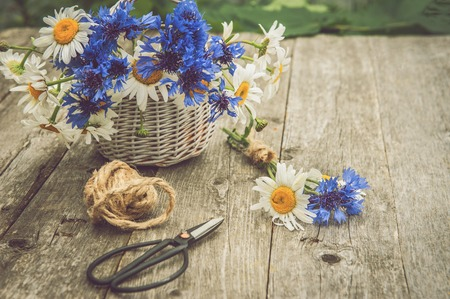 Bouquets of beautiful wild flowers of daisies and cornflowers on a wooden old background. Stock Photo
