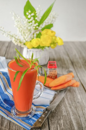 Fresh homemade vegetable juice from carrots and tarragon in a glass Cup. With carrots and yellow flowers.