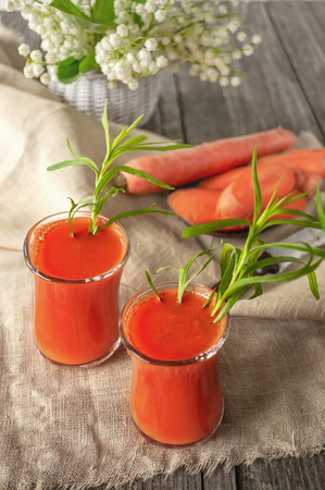 Fresh homemade carrot juice into two glass cups. With carrot and white flowers.