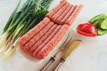 Chevapchichi is a national Balkan dish. Close up a row of fresh raw beef kebabs on a white rectangular platter.