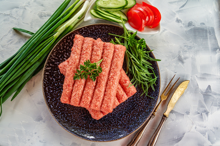 Chevapchichi is a national Balkan dish. Close up a row of fresh raw beef kebabs on a black plate. Copy space Imagens