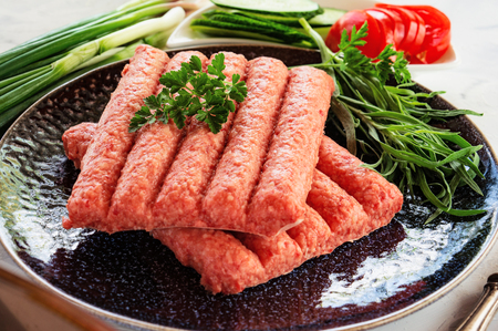 Chevapchichi is a national Balkan dish. Close up a row of fresh raw beef kebabs on a black plate. Close-up.