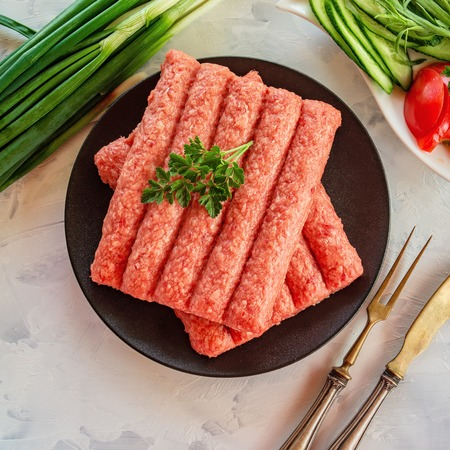 Chevapchichi is a national Balkan dish. Close up a row of fresh raw beef kebabs on a black plate. Imagens