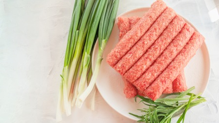 Chevapchichi is a national Balkan dish. Close up a row of fresh raw beef kebabs. Imagens