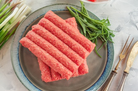 Chevapchichi is a national Balkan dish. Close up a row of fresh raw beef kebabs on a plate. Copy space.
