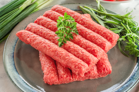 Chevapchichi is a national Balkan dish. Close up a row of fresh raw beef kebabs on a plate. Close-up