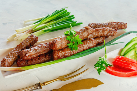 grilled Cevapcici is a Balkan national dish. Close the row of fried beef kebabs on a white rectangular dish with vegetables.