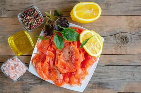 Raw marinated trout fillet and salmon slices with lemon slices on a white plate.