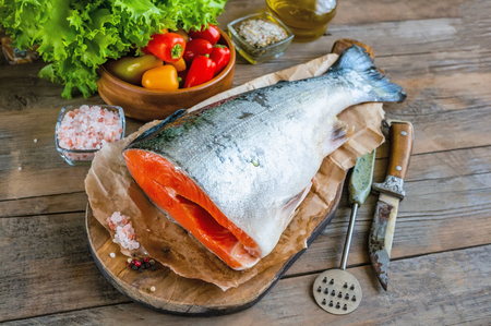 Delicious salmon fillet, rich in omega-3 oil, aromatic spices vegetables and lemon on fresh lettuce leaves on wooden background. Healthy food, keto diet and cooking background