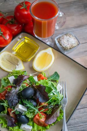 Bord met keto dieetvoedsel. Gehakte groenten voor het ketogeen dieet op een bord. Tomaten, salade met rucola, avocado en olijven. Lunchen met keto. Close-up, selectieve focus