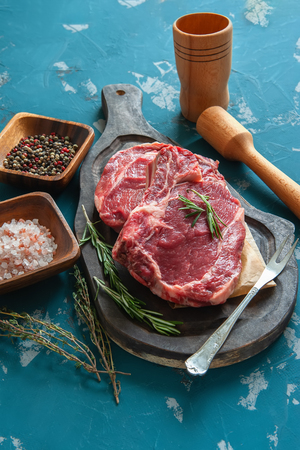 Cutting beef for grilling on a wooden cutting Board with Bay leaf, rosemary for marinade in a rustic style