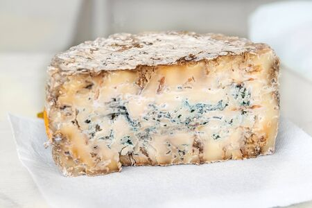 A slice of blue aged delicatessen Stilton cheese on a white table. Farm quality products.