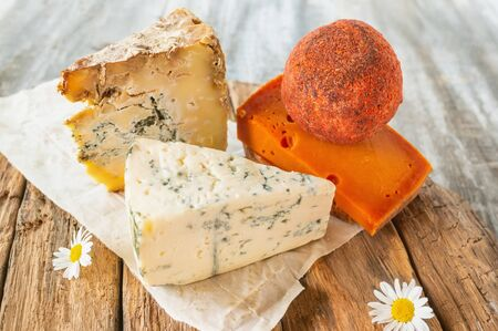 Delicatessen spicy cheeses of different varieties. Red cheddar, Dor blue, Stilton, Belper knoll on a beautiful textured wooden background. Spicy appetizer for gourmets. Selective focus. Stock Photo