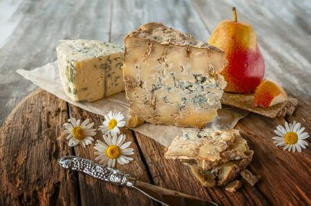 A slice of blue aged Stilton cheese on a wooden table. Cheese is served with a beautiful ripe pear. The quality of farmers ' agricultural products. Delicious English cheeses from Russian farmers.