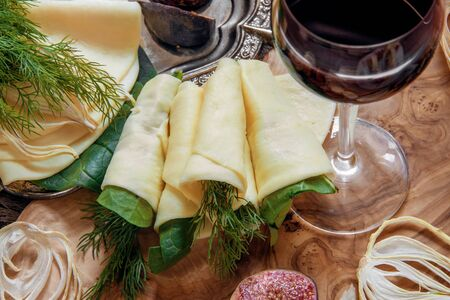 Rolls of thin pancake cheese Suluguni with dill and spinach on a beautiful Board made of natural olive wood. Diet and weight management.