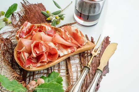 the aroma of ham and spices, thinly sliced on a white table with bread antique Cutlery and red wine.