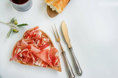 ham and flavor spices, thinly sliced on a white table with bread. close up. Copy space. Stok Fotoğraf