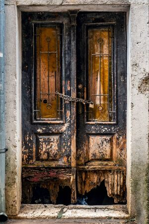 An old brown door in an old cracked stone wall. European street.