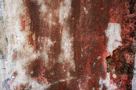 Original background of natural cement plaster on red textured wall with cracks.
