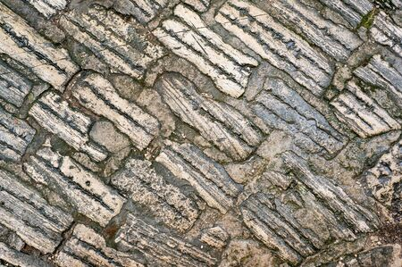 Original background of natural ancient large stone with texture of cracks and bricks. The old cobblestones in Europe.
