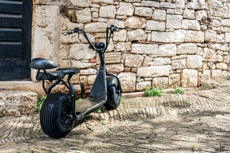 An old black Scooter is parked on the street by the stone wall. Urban eco-friendly transport.