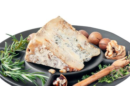 A slice of blue aged Stilton cheese on a wooden table.