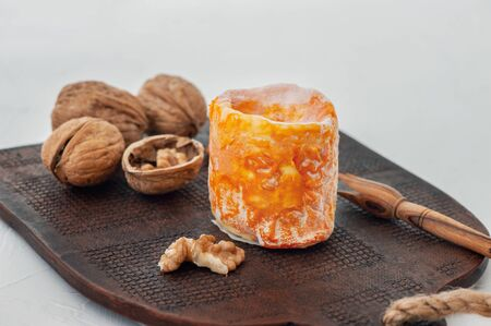 French Epoisses soft cheese with white mold with a beautiful orange peel on a brown plate
