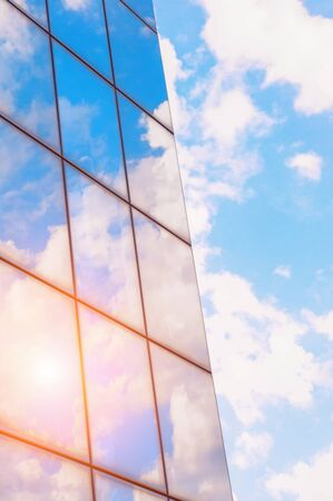 A skyscraper or modern building in a city with clouds and sunlight reflected in the Windows. Stok Fotoğraf