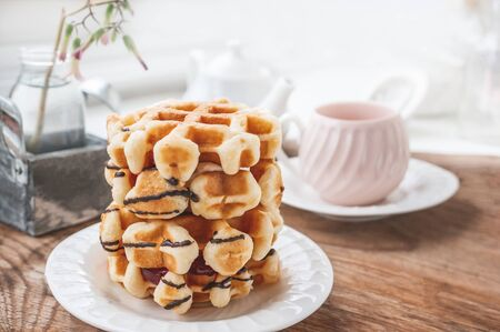 Fresh round Belgian waffles with a layer of jam poured with chocolate on a white plate with a Cup of tea. Close up.