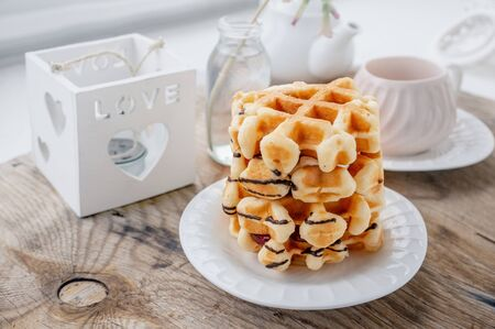 Delicious Fresh round Belgian waffles with a layer of jam poured chocolate on a white plate with a Cup of tea. Close up. Zdjęcie Seryjne