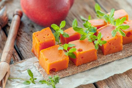 The pieces of red cheddar, on a beautiful textured wooden background with sprigs of savory and the peaches is a spicy snack for gourmets. Delicacies, spicy cheeses.Selective focus. Imagens