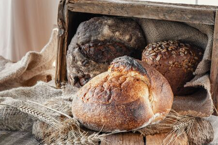 Beautiful loaves of wheat leaven bread with an assortment of grains and seeds on a plate on the edge of the canvas. Homemade cakes, handmade. Close up. Lifestyle.