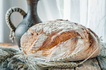 Beautiful loaves of bread on a leaven of white wheat on a plate on the edge of the canvas. Homemade cakes, handmade. Close up.