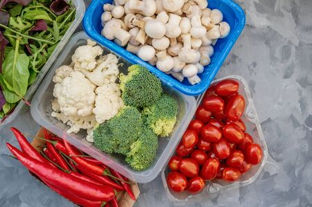 Mixed cauliflower and broccoli vegetables, baby salad, mushrooms, peppers, tomatoes and chili in lunch box on wooden background in rustic style.