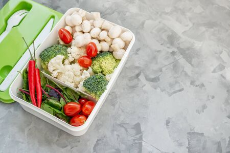 Mixed cauliflower and broccoli vegetables, baby salad, mushrooms, peppers, tomatoes and chili in lunch box on wooden background in rustic style. Copy space Archivio Fotografico