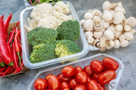 Mixed cauliflower and broccoli vegetables, baby salad, mushrooms, peppers, tomatoes and chili in lunch box on wooden background in rustic style. Close up Archivio Fotografico