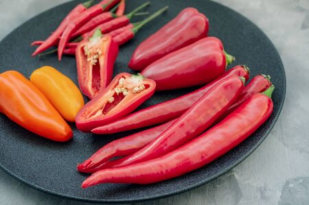 Colorful mix of the freshest and hottest chili peppers and Bulgarian colored pepper on a black plate.